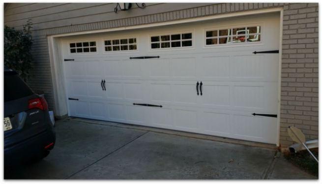 White garage doors with a car parked in front.