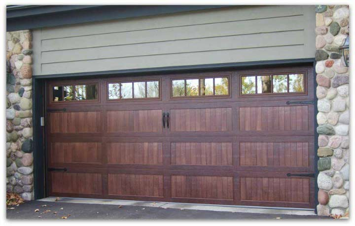 Stone sided garage with dark wood garage doors.