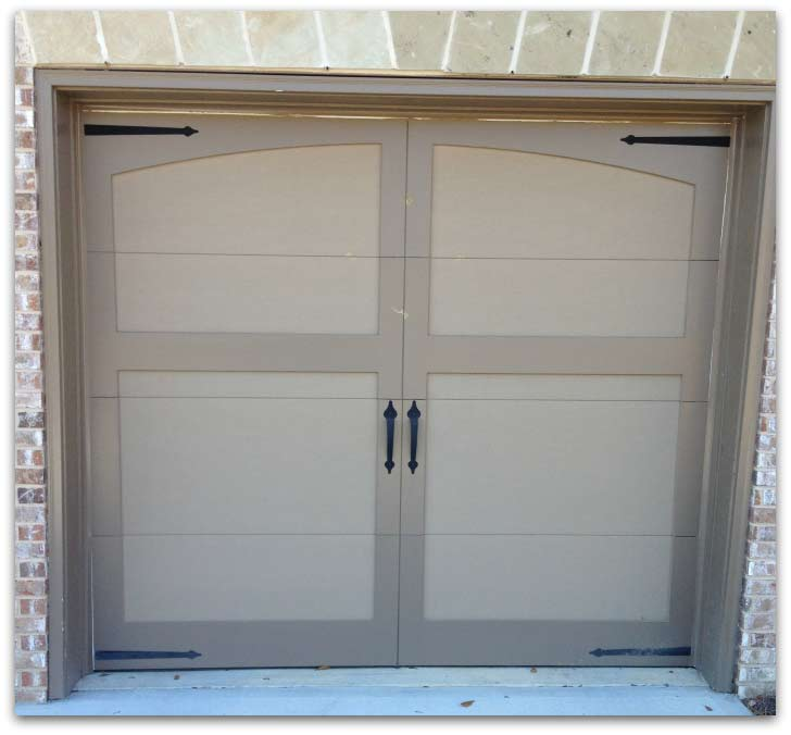 Brick home with carriage style garage doors.