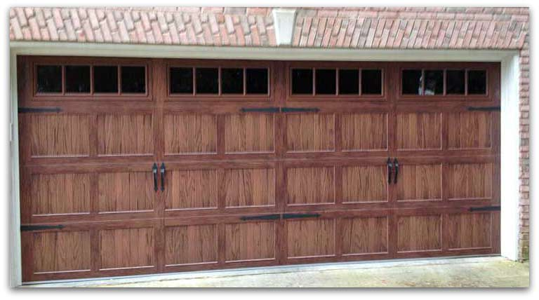 Brick home with wooden garage doors.